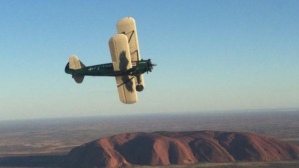 El Boeing Stearman, sobrevolando la famosa roca de kevin Ayer, en Australia